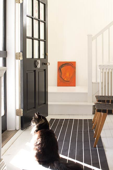 A white entryway with black door opens to contemporary black chairs and black throw rug.