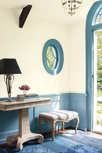 A welcoming entryway includes off-white walls with blue wainscoting and door trim.