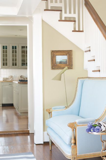 An entryway features a light blue traditional settee against a white staircase.