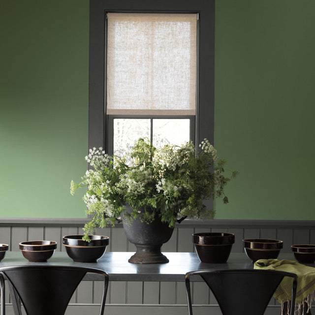 Green painted walls lighten this dining room with dark grey trim, wainscoting and table.