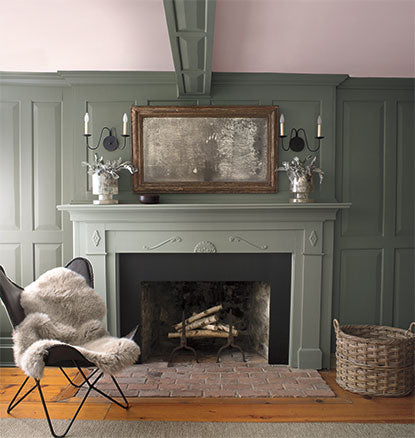 A green-painted living room with matching green mantel and fur throw.