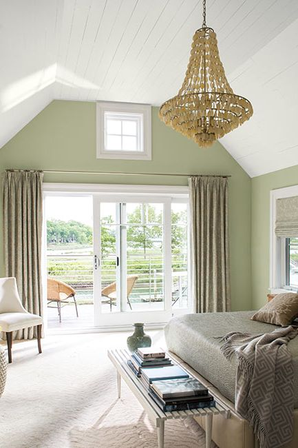 A light green-painted master bedroom with chandelier and glass sliding doors leading to outside deck.