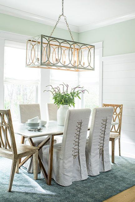A delicate green-painted dining room with pendant light and teal rug.