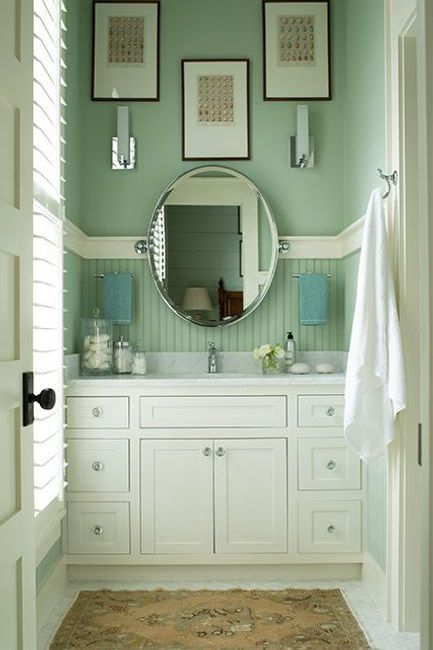 A green-painted bathroom with white built in sink cabinets and marble countertop.