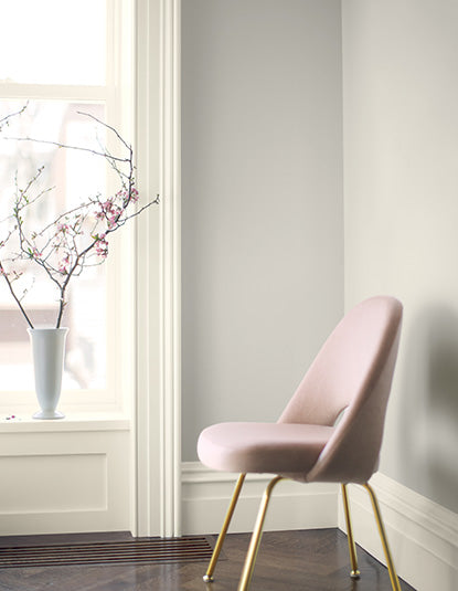 A pink chair frames a wall painted in Balboa Mist OC-27.