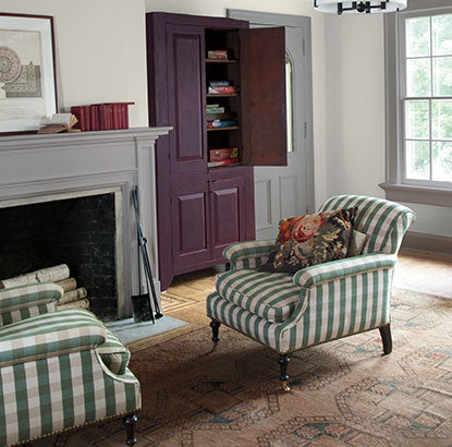 A sitting area with walls painted in Barren Plain 2111-60, fireplace, and two green striped chairs.