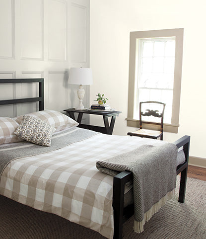 A white bedroom with panelled walls painted in Classic Gray OC-23.