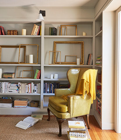 A study with greige-painted walls features alcove bookcases with books and frames, a cozy chair, and golden blanket.