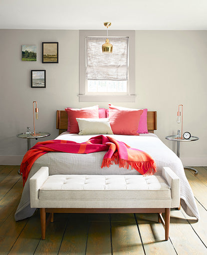 A neutral colored bedroom with walls painted in Natural Cream OC-14, bold red throw pillows, and blanket.