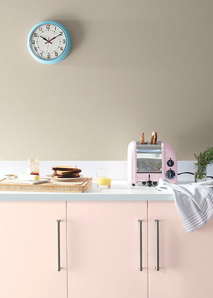 Greige walls with light pink cabinets and white countertops featuring kitchen appliances and a small blue wall clock.