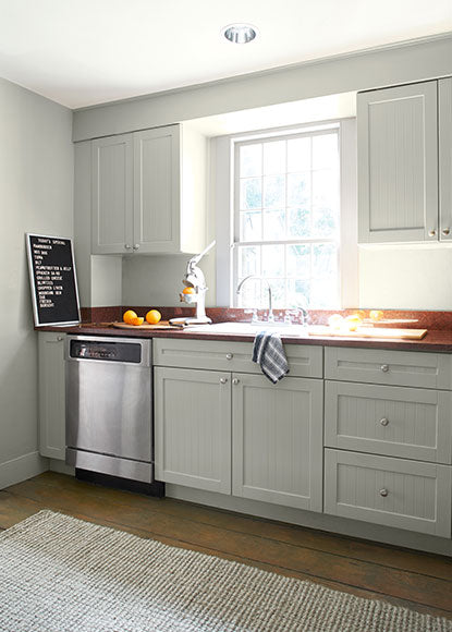 An airy kitchen with walls, cabinets and trim painted in Titanium OC-49, a light greige.