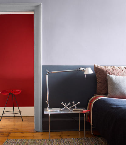 A bedroom featuring two shades of gray is beautifully contrasted by a red hallway beyond its open door.