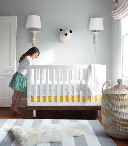 A pale blue gray nursery features a white crib overseen by a big sister.