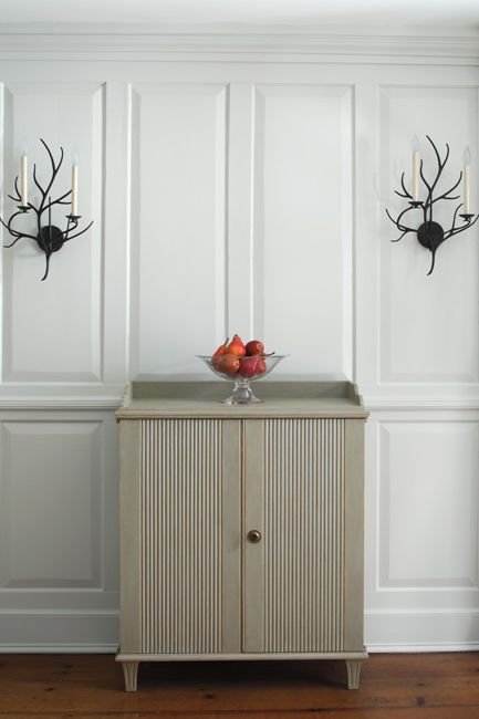 Panelled gray-painted walls frame a chest centered between candle sconces.