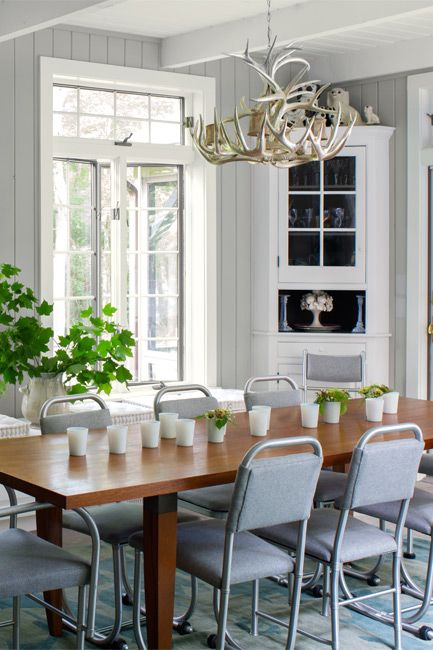 An airy dining room in grays and whites invites guests to the table.