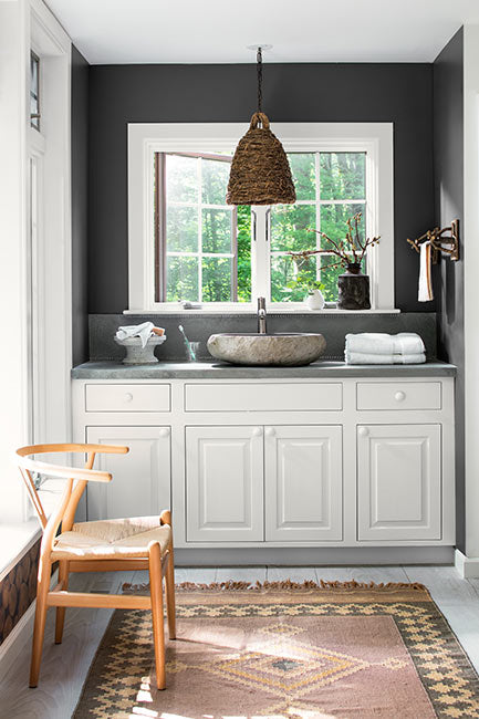 A white bathroom vanity with stone vessel sink underneath a charcoal gray wall with window.