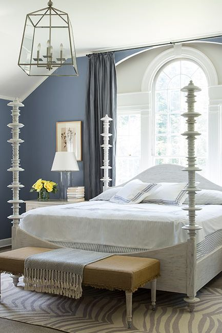 A master bedroom with gray-blue walls is complemented by a white angled ceiling.