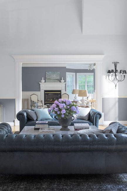 A serene living room in a combination of white and gray paint features two large leather couches.