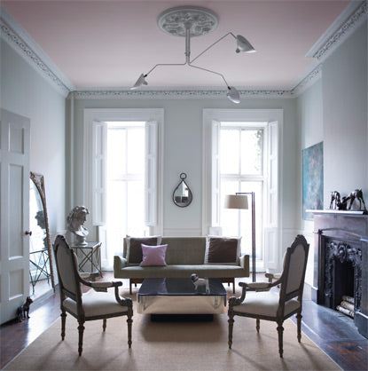 A living room in a blue gray paint is accented by a pale pink ceiling.