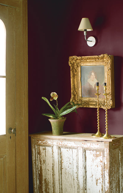 This light-flooded entryway features two tapered candles and a potted flower on top of a weathered antique table set against a deep, plum-colored wall.