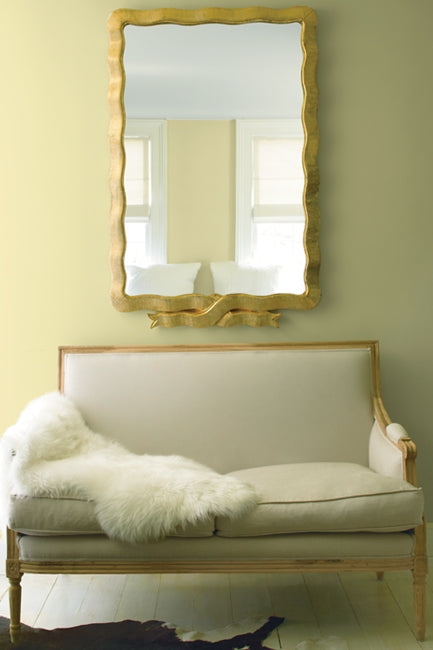 A delicate, cream-colored settee accented with a white fur throw beckons underneath an oversized, gold-framed mirror with a black and white cowhide rug on the floor.
