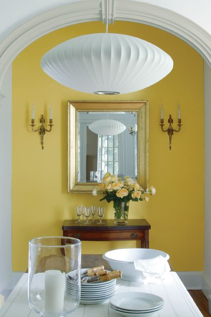 A dining room features a contemporary lamp at center, a contrast to the traditional furnishings including a white wooden farmhouse table, antique white chair, ornate sconces and arched windows seen in the neighboring hallway.