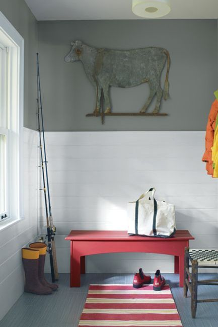 A mudroom features a large illustration of a sheep against a gray-hued painted wall panel; a red bench and striped red and white rug add a punch of color in contrast to white-tiled walls.
