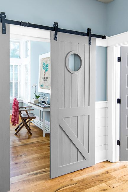 Blue painted walls in home office with gray painted barn sliding doors
