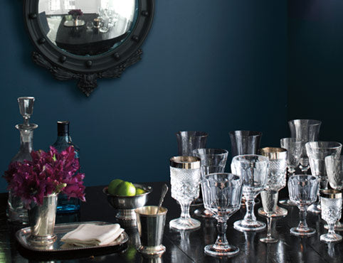 A dark blue-painted dining room wall frames ornate glasses on a table.