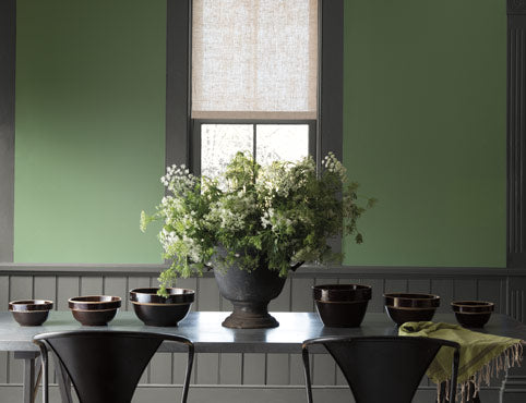 Green painted walls lighten this dining room with dark gray trim, wainscoting and table.