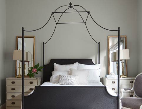 A light gray bedroom features a wrought iron four poster bed.