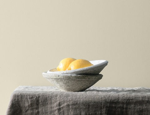 Lemons in a gray clay bowl resting on a table with a neutral wall backdrop