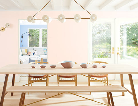Light pink-painted dining room walls with a long wooden table, matching chairs and bench seating.