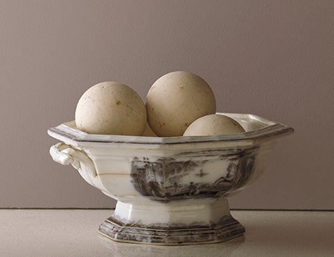 A decorative rustic bowl against a painted wall in Smoked Oyster 2109-40.