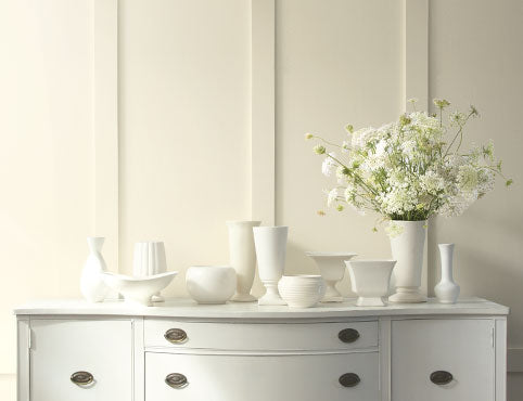 A warm white painted wall creates a soft backdrop for vases and flowers atop a traditional console.