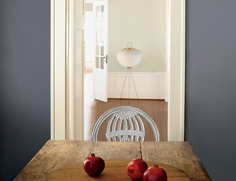 Rustic plank table with gray-blue wall and pomegranates