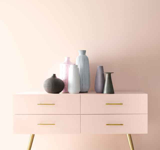 A light pink wall frames a pink console with gold handles and multiple vases