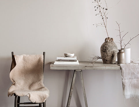 Gray dining area featuring a rustic table with books, vases, and branches, and chair topped with white fur blanket.