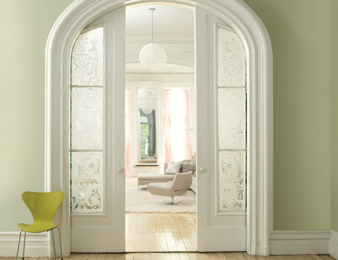 Sliding doors with etched window panes open to a serene white living room.