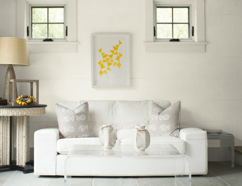 A bright sitting room with white shiplap walls accented by neutral fabric furniture and accessories.