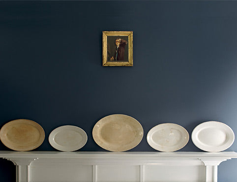 A white wood mantel features five decorative plates of varying sizes in neutral tones horizontally placed against a blue wall; a small antique painting hangs above.
