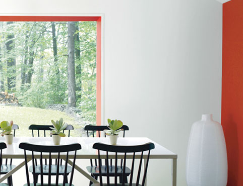 White dining room with orange accent wall and black dining chairs