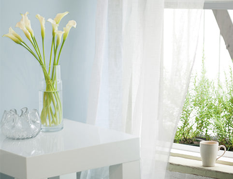 A vase of flowers sits on a small, square bedside table next to an open window framed by a gauzy white curtain and a light blue wall.
