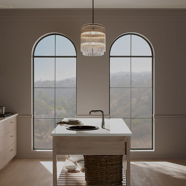 A kitchen with beige walls, two large arch windows, and an island with a sink.