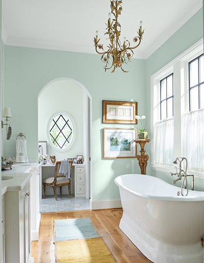 Airy bathroom with pastel green walls, chandelier, soaking tub, sink and cabinets, wall art, large windows, and a desk and chair.