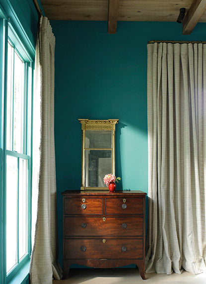 Green-painted bedroom with wooden dresser, gold mirror, and floor-length curtains.
