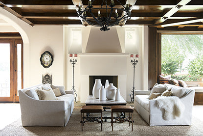 Large open living room with coffered ceiling, chandelier, white seating, leather stools, candelabras, and large windows.