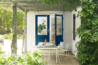 A back porch covered in ivy with blue-painted doors, white walls, and chair and table.