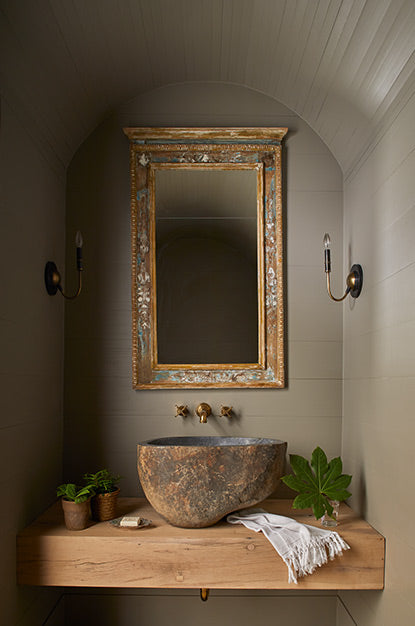 Vignette of a bathroom alcove featuring curved ceiling, large mirror, a sink carved from rock, wall lights, and plants.