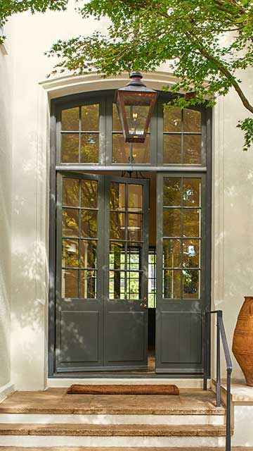 An exterior entryway featuring a large door with many windows, stairs, terra cotta pots, and a tree.